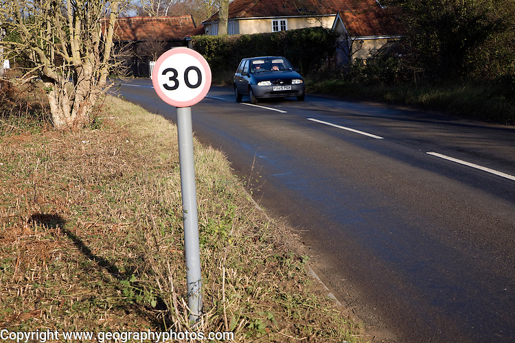 Car driving in 30 mph zone through village