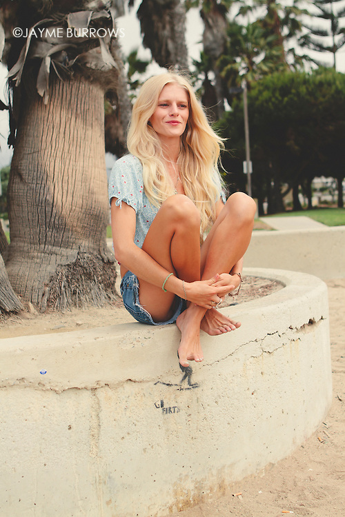 Blonde woman hanging out by the beach.