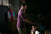 51 year old Goh Kuam Boon, a former pig farmer and a  survivor of the Nipah virus spends time with his grandson in the kitchen of their house in Bukit Pelandok in Nageri Sembilan, Malaysia on October 16th, 2016. <br /> In September 1998, a virus among pig farmers (associated with a high mortality rate) was first reported in the state of Perak in Malaysia. Dr. Chua investigated and discovered the virus and it was later named, Nipah Virus. The outbreak in Malaysia was controlled through the culling of &gt;1 million pigs.