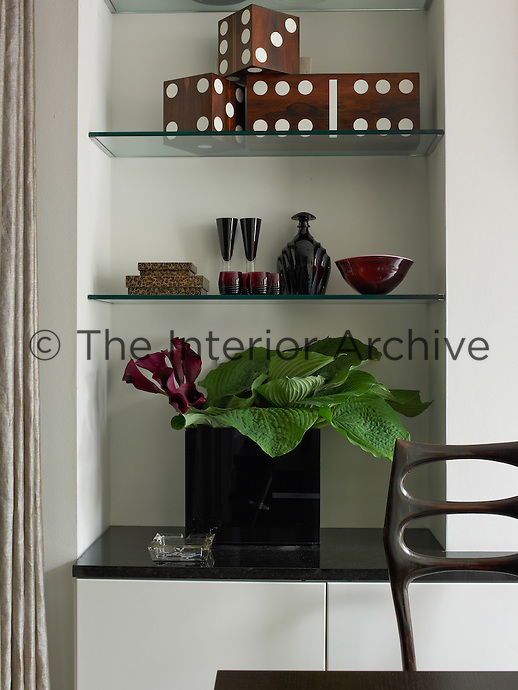 Glass shelves situated in an alcove add to the feeling of spaciousness and light in the dining room