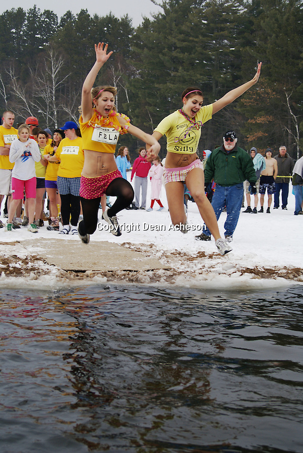 Two teenage girls jump into the frigid waters of St. Germain Lake, near St. Germain, WI., during the annual Polar Bear Plunge Jan. 5, 2008. The event raises money for a local charity and more than 100 participants become, or renew, their polar bears.