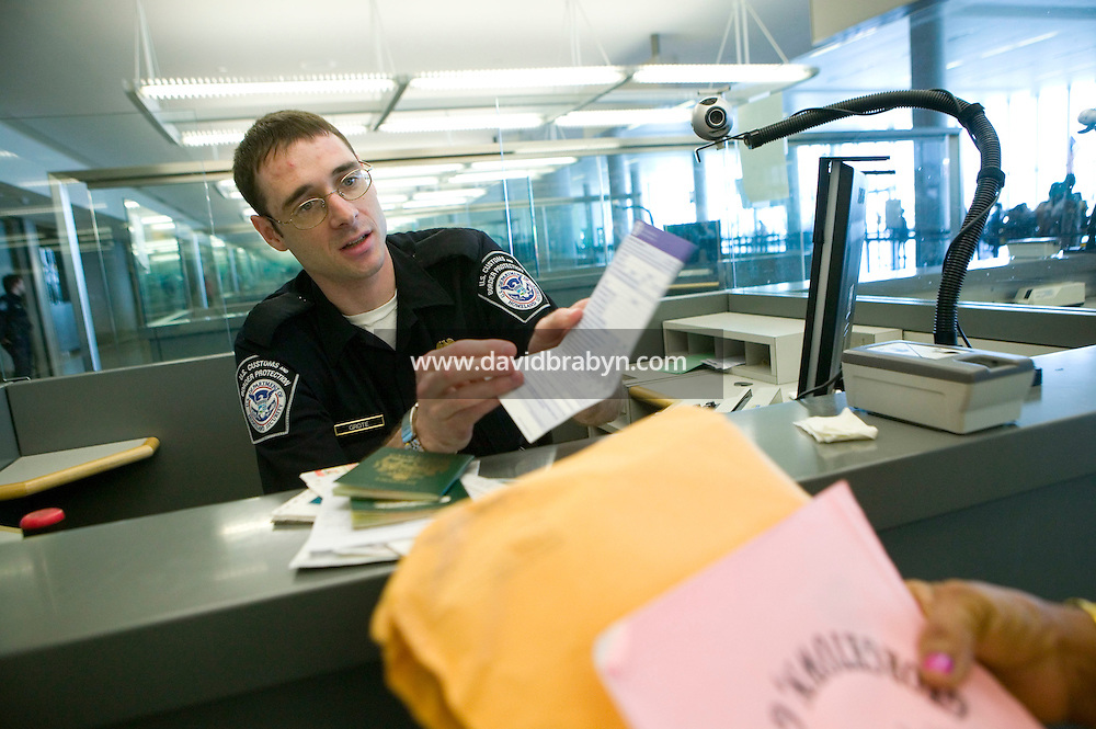 11 April 2006 - New York City, NY - CBP officer Charles Grote (L) processes passengers from Guyana at a passport control station in Terminal 4 at JFK airport in the Queens borough of New York City, USA, 11 April 2006.
