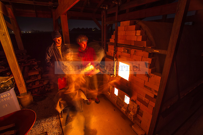 David Kring (left) of Kentucky Mud Works and Marvin Puckett (right), who is a graduate assistant at Morehead University, watch Senior Sculpture major Katelyn Gabbard feed some logs into the kiln. The kiln was constantly monitored, stoked, and fed wood 24 hours a day for 3 days straight. in Lexington, Ky., on Saturday, November, 17, 2012. Photo by James Holt | Staff