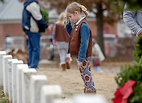 STAFF PHOTO JASON IVESTER --12/13/2014--<br /> Emma Hardman, 8, of Lowell, salutes after placing a wreath at a headstone on Saturday, Dec. 13, 2014, following the Wreaths Across America ceremony at the Fayetteville National Cemetery. Wreaths were placed at each of the 7100 veteran graves in the cemetery.