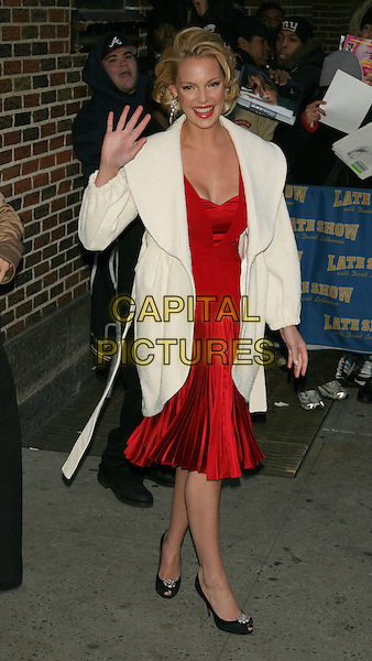 "KATHERINE HEIGL.(promoting the film, ""27 Dresses"").Appearance on the ""Late Show with David Letterman"" at the Ed Sullivan Theater, New York, NY, USA..January 16th, 2008.full length white cream coat wide collar hand palm waving red satin silk drop waist dress pleats pleated black shoes .CAP/LNC/TOM.©TOM/LNC/Capital Pictures"