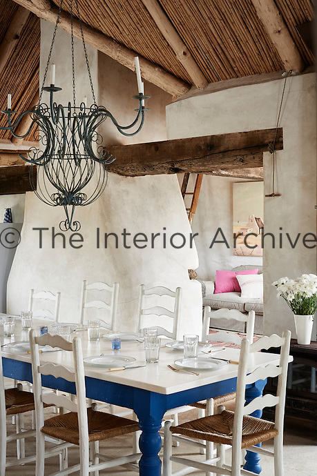 A country dining room with a wood and bamboo ceiling and stone walls. A wrought iron chandelier hangs above a white and blue painted table set for lunch.