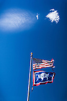 The U.S. and Wyoming flags fly against a blue sky with whisps of clouds overhead.