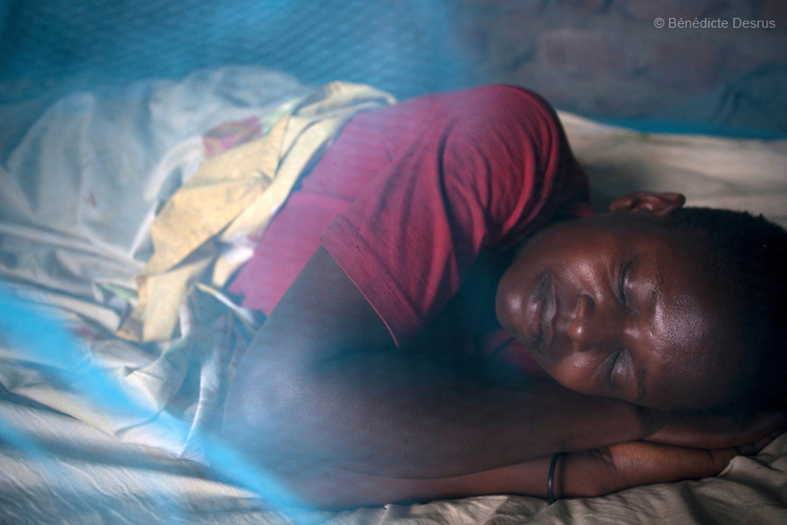 15 april 2010  Busagazi, Uganda - Baluka Dulorensi sleeps under a mosquito net she set up to prevent malaria. Malaria is a mosquito-borne infectious disease. The disease kills over a million people in the world every year, mostly children and pregnant women. Malaria transmission can be reduced preventing mosquito bites by using mosquito nets and insect repellents, or by mosquito-control measures such as spraying insecticides inside houses and draining standing water where mosquitoes lay their eggs. Photo credit: Benedicte Desrus