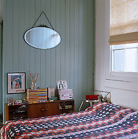 A collection of personal memorabilia is displayed on top of the sideboard in the simple bedroom