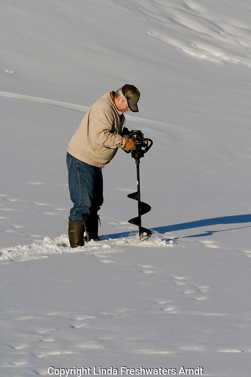 Man using auger for ice fishing