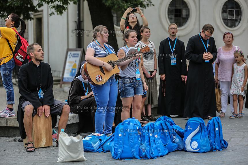 World Youth day Krakow 2016<br /> Due giovani suonano e cantano e prete in preghiera