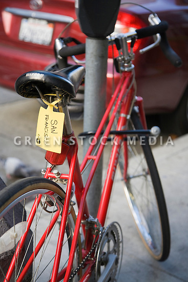A close up of a bike with a yellow Caltrain bike tag. The bike tags are used by Caltrain riders to identify what station their bike is getting off at. This ensures proper stacking in the Caltrain bike car. San Francisco, California, USA