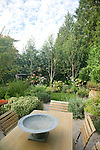 A mixed border of trees, shrubs and perennials provides privacy for the outdoor dining and lawn areas in this Seattle yard.