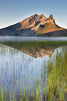 Mount Sukakpak of the Brooks Range mountains reflects in a tundra pond on an autumn morning, Arctic, Alaska.