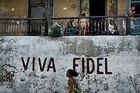 A Cuban woman walks in front of a propaganda writing, celebrating the Cuban leader Fidel Castro, in Santiago de Cuba, Cuba, 31 July 2008. About 50 years after the national rebellion, led by Fidel Castro, and adopting the communist ideology shortly after the victory, the Caribbean island of Cuba is the only country in Americas having the communist political system. Although the Cuban state-controlled economy has never been developed enough to allow Cubans living in social conditions similar to the US or to Europe, mostly middle-age and older Cubans still support the Castro Brothers' regime and the idea of the Cuban Revolution. Since the 1990s Cuba struggles with chronic economic crisis and mainly young Cubans call for the economic changes.