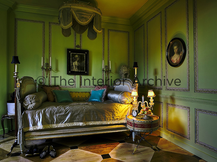 An elegant Empire-style bed upholstered ini dove grey silk against green painted panelling in the French-style