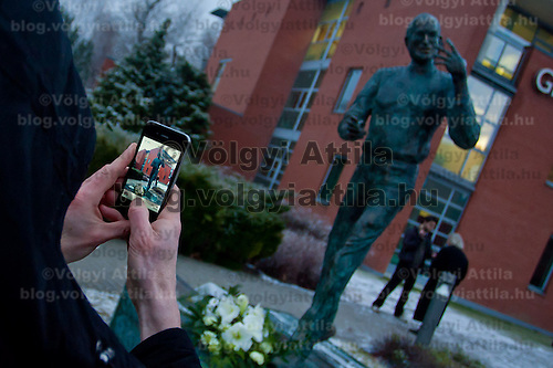 Viewer takes a photo with an iPhone after the inauguration ceremony of the first ever life-size bronze statue of late Apple leader Steve Jobs in Budapest, Hungary on December 21, 2011. ATTILA VOLGYI