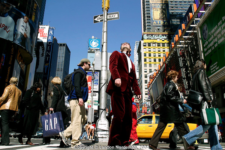 "NEW YORK - APRIL 3: Klaus Wunderhits (in the red velvet suit) from Norway takes in the view from the median at 45th Street between Broadway and 7th Avenue in Times Square April 3, 2004 in New York City. Wunderhits visited New York to shoot a music video of himself for his song called, ""Let's Have A Cheer,"" which is about a crazy man walking around New York having a good time. His only comment about Times Square was, ""I don't like that naked cowboy guy, really."" (The Naked Cowboy, who plays his guitar in Times Square almost every day is pictured in rear center.) Times Square's 100th birthday is April 8, 2004. On April 8, 1904, Mayor George McClellan signed a resolution changing the name of Long Acre Square to Times Square. Times Square, a living icon of popular culture, is one of the most familiar and most frequently reproduced fragments of urban real estate on the planet.  (Photo by Landon Nordeman, 2004)."