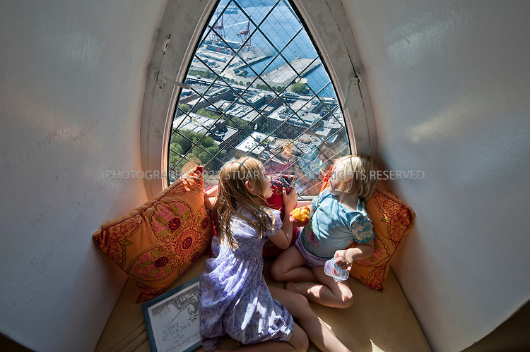 9/27/2010--Seattle,WA, USA..Petra Franklin's  daughters Simone, 6 (left), and Naomi, 3 (right)  sit in the bedroom window of her parents room on the first floor of Petra Franklin's penthouse apartment in Smith Tower in Seattle. Outside is Pioneer Square and the Port of Seattle...Smith Tower, located in Seattle's Pioneer Square neighborhood, is the oldest skyscraper in the city. Completed in 1914 it has 38 floors and  remained the tallest building on the West Coast until the Seattle Space Needle overtook it in 1962. The tower is 462 ft (143 meters) from street level to the top of the pyramid with a small glass lighthouse at the top...Petra Franklin, 46 and her husband David Lahaie, 51 live in the pyramid on top of Smith Tower with their two daughters Simone, 6, and Naomi, 3. Franklin is co-founder and general partner of Vault Capital, a venture capital fund with offices in Smith Tower..Copyright © 2010 Stuart Isett. All rights reserved.