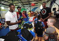 NWA Democrat-Gazette/ANDY SHUPE<br /> Manuale Watkins (from left), Jimmy Whitt and Moses Kingsley, all members of the University of Arkansas men's basketball team, laugh Wednesday, July 29, 2015, with students as they hand out backpacks at the Boys and Girls Club of Fayetteville. The backpacks were filled with school supplies as needed, all provided by Dwelling Place Church, the Upsilon Chapter of Omega Psi Phi, the Gamma Eta Chapter of Omega Psi Phi, the Boys and Girls Club of Fayetteville, Walgreens, the University of Arkansas men's basketball team, and the Ronnie Brewer Foundation. After receiving a backpack and school supplies, the students spent time with the student-athletes and Brewer.