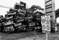 Italy. Lombardia Region. Levate. Cobea company. Plant for separation iron and non-iron materials. Pile of derelict motor vehicles. Cars about to be ground out in order to recycle the metals. A sign advice to wear a safety helmet and be careful with various materials falling from the moving cranes. © 1993 Didier Ruef .