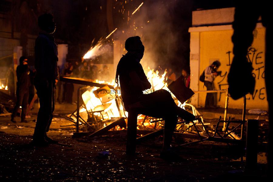 ©VIRGINIE NGUYEN HOANG.Egypt,Cairo.26/01/2013..Clashes have erupted between protesters and security forces near the Interior Ministry in downtown Cairo.Several policemen went to the top of an old building to fire tear gas and hurl stones at protesters. Meanwhile, dozens of protesters stood on top of the concrete wall separating Tahrir Square and Sheikh Rehan Square to hurl stones at policemen..Other protesters threw Molotov cocktails at buildings near the ministry headquarters, setting one building on fire..Des affrontements ont eclate entre les manifestants et les forces de sécurite pres du ministere de l'Intérieur du centre-ville du Cairo. PLusieurs policiers se trouvaient au sommet d'un immeuble ancien pour tirer du gaz lacrymogene et lancer des pierres sur les manifestants. Pendant ce temps, des dizaines de manifestants repondaient egalement par jet de pierres sur les policiers..D'autres manifestants ont jete des cocktails Molotov sur les batiments proches du siège du ministère et mis un bâtiment en feu.