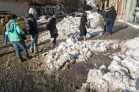 Pedestrians slog through puddles of slush and snow during their morning commute at street crossings with snow dam clogged storm drains in the Chelsea neighborhood of New York on Monday, January 25, 2016. Winter Storm Jonas dumped 26.8 inches onto Central Park making it the second-highest amount since records started in 1869 and with temperatures rising above freezing some of that snow will melt. (© Richard B. Levine)