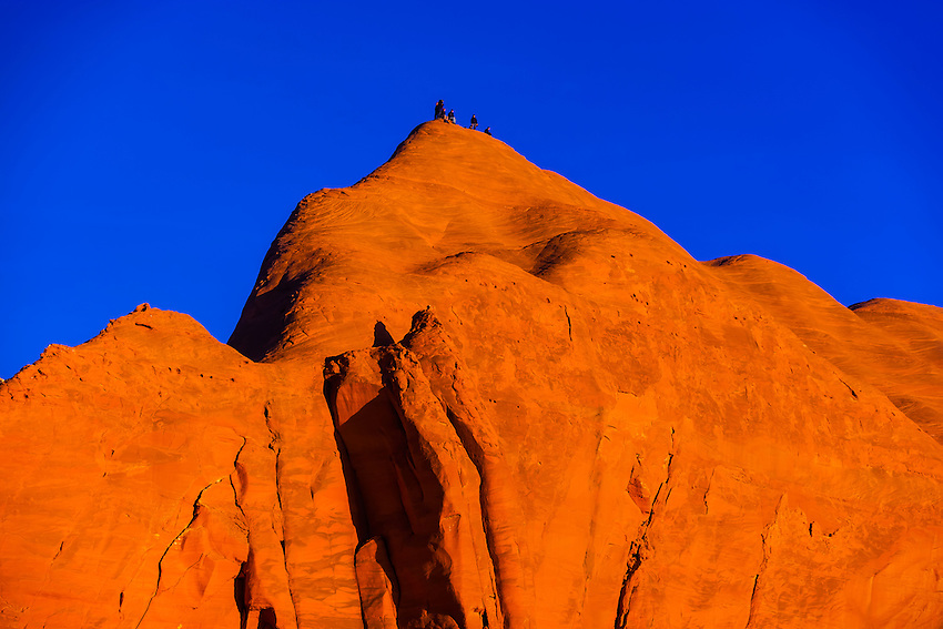 People atop a huge monolithic rock during the Red Rock Balloon Rally, Red Rock State Park, near Gallup, New Mexico USA.