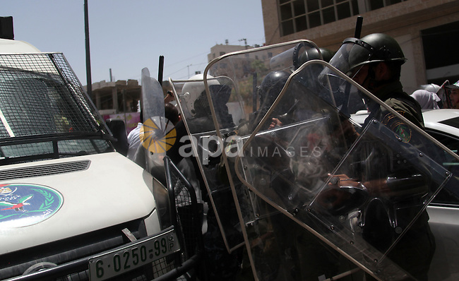 Palestinian riot police stand guard as demonstrators shot slogans during a protest to show solidarity with prisoners on hunger strike in Israeli jails, in the West Bank city of Hebron on June 20, 2014. Israel is to rush through a bill allowing force-feeding of hunger-striking prisoners, a newspaper reported on June 17, 2014 as 80 Palestinian inmates were hospitalised after refusing to eat for nearly two months. Photo by Mamoun Wazwaz