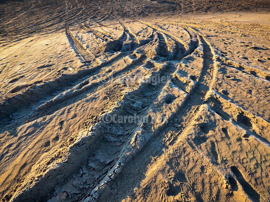 Tire tracks at sunrise at the Winnemucca Dunes along US-95 north of town in the late winter with snow.