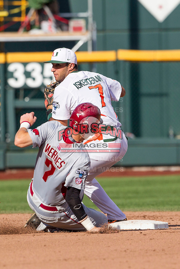 Miami Hurricanes second baseman George Iskenderian (7) turns a double play during the NCAA College baseball World Series against the Arkansas Razorbacks  on June 15, 2015 at TD Ameritrade Park in Omaha, Nebraska. Miami beat Arkansas 4-3. (Andrew Woolley/Four Seam Images)