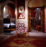 A Louis XVI-style chair upholstered in a modern fabric stands against a Moroccan tiled wall in the entrance to this bedroom