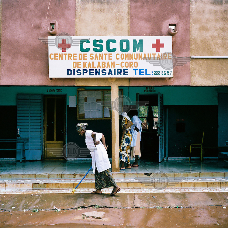 A woman cleans outside the front of a health centre in Bamako.