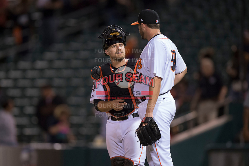 Fresno Grizzlies catcher Tim Federowicz (26) talks to relief pitcher James Hoyt (58) after a Pacific Coast League game against the Salt Lake Bees at Chukchansi Park on May 14, 2018 in Fresno, California. Fresno defeated Salt Lake 4-3. (Zachary Lucy/Four Seam Images)