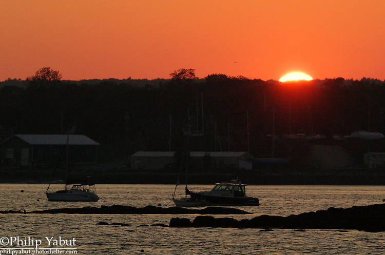 The sun disappears under the treeline over Rockland, Maine.