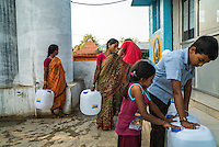 Customers gather to buy safe water from the iJal station in Peddapur, a remote village in Warangal, Telangana, India, on 22nd March 2015. Safe Water Network works with local communities that live beyond the water pipeline to establish sustainable and reliable water treatment stations within their villages to provide potable and safe water to the communities at a nominal cost. Photo by Suzanne Lee/Panos Pictures for Safe Water Network