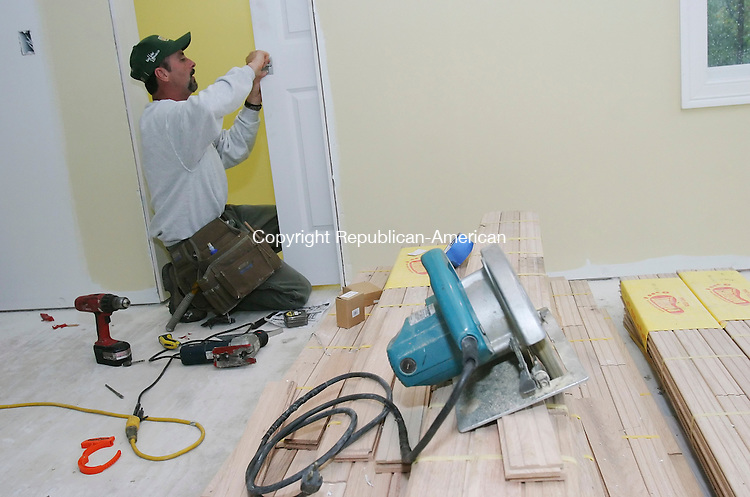 NORTHFIELD,  CT 13 October 2005 -101305BZ01- Mark Bourdeau, a Katahdin Cedar Home builder, installls locks on a door inside a home he's building in Northfield.  <br />  Jamison C. Bazinet / Republican-American