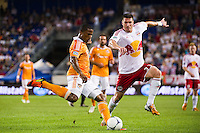 Jermaine Taylor (4) of the Houston Dynamo clears the ball as Kenny Cooper (33) of the New York Red Bulls looks to block. The New York Red Bulls defeated the Houston Dynamo 2-0 during a Major League Soccer (MLS) match at Red Bull Arena in Harrison, NJ, on August 10, 2012.