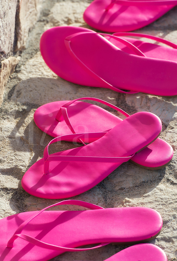 Matching pairs of hot pink sandals.
