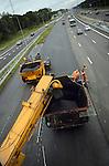 NIEUWEGEIN - Op de snelweg A2 tussen Nieuwegein en IJsselstein is Heijmans Wegenbouw uit Rosmalen bezig met het asfalteren van de snelweg. Vanwege de aanleg van extra rijstroken en nieuwe afritten, wordt de zomerperiode gebruikt om de gehele snelweg van nieuw asfalt te voorzien, nadat eerder ondermeer nieuwe vangrails is gemonteerd. Terwijl 's avonds de helft van de rijbaan wordt afgesloten om het asfalt te verwijderen, wordt overdag het nieuwe wegdek aangelegd. Vanwege de veiligheid van de wegwerkers is de maximum snelheid beperkt, en zijn geleidebakens geplaatst. COPYRIGHT TON BORSBOOM