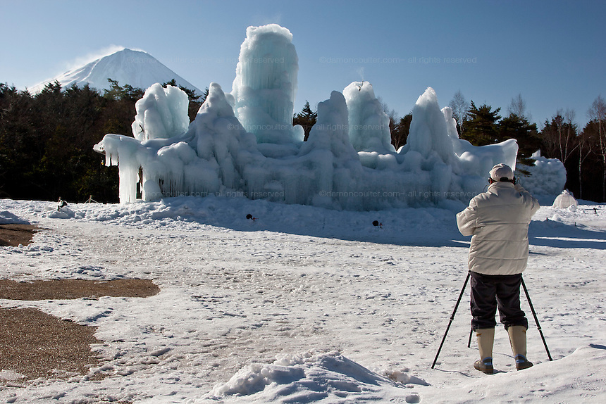 A photographer uses a tripod to take photographs of a snow capped Mount Fuji behind a frozen fountain in Kawaguchiko. Japan, Wednesday February 13th 2008