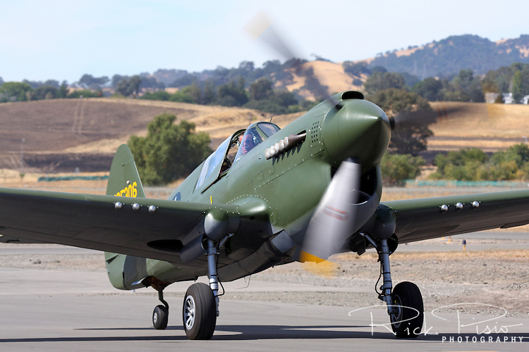 A Curtis P-40N Warhawk taxies on the ramp after arriving at a fly-in at the Nut Tree Airport in Vacaville, California. The Curtiss P-40 first flew in 1938 and was used by the air forces of 28 nations, including those of most Allied powers during World War II, and remained in front line service until the end of the war. When production ceased in November of 1944 13,738 had been built, all at Curtiss-Wright Corporation's main production facility at Buffalo, New York.