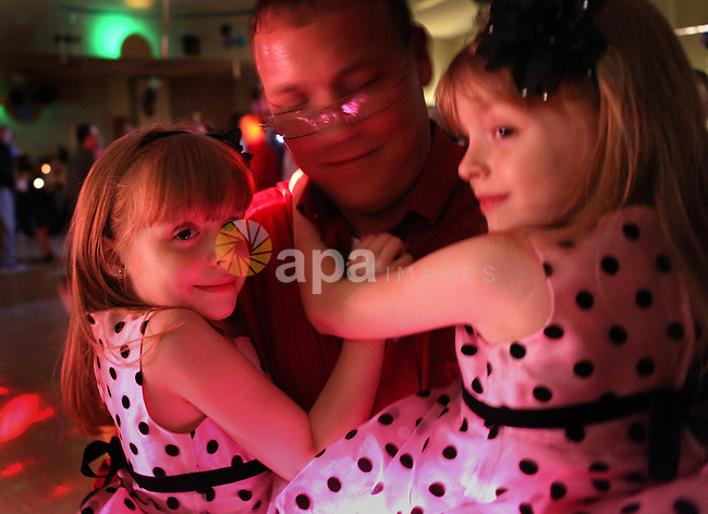 Feb. 3, 2012 - Brooksville, Fl - MAURICE RIVENBARK | Times.HT_349657_rive_DANCE.(02/03/2012, BROOKSVILLE) James Norris holds his 6 year-old twin daughters Dalaney and Nakayla (l-r in the photo) as the trio dance Friday night during the Hernando County Recreation Department's annual Father-Daughter Dance.  The event, held at St. Anthony Catholic Church in Brooksville, featured a dance on Saturday night also. (Credit Image: © Tampa Bay Times/ZUMAPRESS.com)