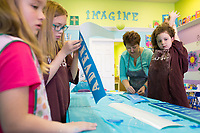 NWA Democrat-Gazette/CHARLIE KAIJO Melanie Hewins, owner and artist of Imagine Studios, (center) helps (from left) Haedyn Heckscher, 7, Reese Heckscher, 10 and Finley Boral, 7, create stencil art during a spring break art camp, Monday, March 19, 2018 at the Imagine Studios in Rogers. <br /><br />Melanie Hewing, owner and artist of Imagine Studios, worked as a literacy facilitator at Rogers High School for seven years and during that time discovered a talent and love for creating art through a side business painting murals in children's bedrooms. <br /><br />People began to ask if she would provide art classes for them as word spread. She has had her studio, Imagine Studios, now for seven years where she hosts classes and camps for both kids and adults.