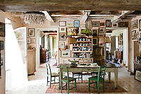 The walls of the large country kitchen are covered in paintings and green distressed chairs surround the wooden table