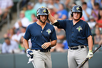 Designated hitter Tim Tebow (15) of the Columbia Fireflies is greeted by Dash Winningham after scoring a run in a game against the Greenville Drive on Thursday, June 15, 2017, at Fluor Field at the West End in Greenville, South Carolina. Columbia won, 7-2. (Tom Priddy/Four Seam Images)