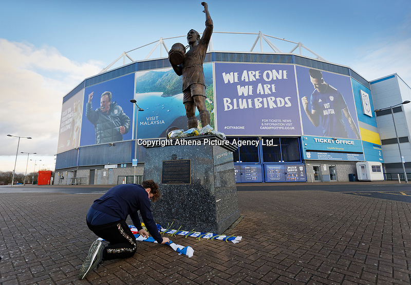 Pictured: A young fan leaves his scarf by the statue of Frederick Charles Keenor outside the Cardiff City Stadium in south Wales, UK. Tuesday 22 January 2019<br /> Re: Premier League footballer Emiliano Sala was on a flight which disappeared between France and Cardiff.<br /> The Argentine striker was one of two people on board the Piper Malibu, which disappeared off Alderney on Monday night.<br /> Cardiff City FC, signed the 28-year-old from French club Nantes.<br /> A search is under way.<br /> A Cardiff Airport spokeswoman confirmed the aircraft was due to arrive from Nantes but said there were no further details.<br /> HM Coastguard has sent two helicopters to help.