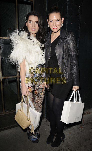 Grace Woodward & Olivia Lee.The InStyle Best Of British Talent party, Shoreditch House, Ebor St., London, England..January 26th, 2012.full length black white beige floral print trousers fur wrap goody bag dress leather jacket tights.CAP/CAN.©Can Nguyen/Capital Pictures.