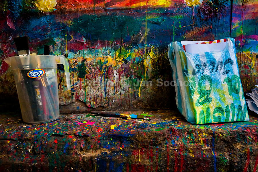 """Clean brushes and folded posters, available to pick up, are seen placed on a splattered kerb in the sign painting workshop in Cartagena, Colombia, 12 December 2017. Hidden in the dark, narrow alleys of Bazurto market, a group of dozen young men gathered around José Corredor (""""Runner""""), the master painter, produce every day hundreds of hand-painted posters. Although the vast majority of the production is designed for a cheap visual promotion of popular Champeta music parties, held every weekend around the city, Runner and his apprentices also create other graphic design artworks, based on brush lettering technique. Using simple brushes and bright paints, the artisanal workshop keeps the traditional sign painting art alive."""