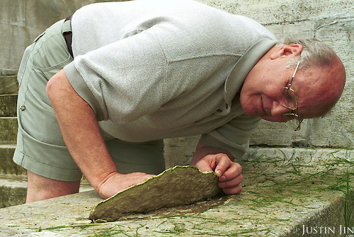 Canadian military official Gerry Carline (pls check name and title with Alan) picks up a piece of broken stone at the base at the memorial.. .Photo taken 10 May 2000 at the Canadian War Memorial at Vimy, France..Credit: Justin Jin